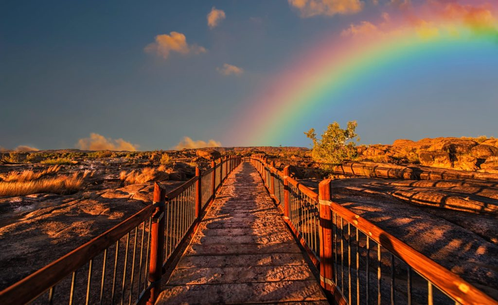 First person view of bridge, with rainbow in the distance at sunset