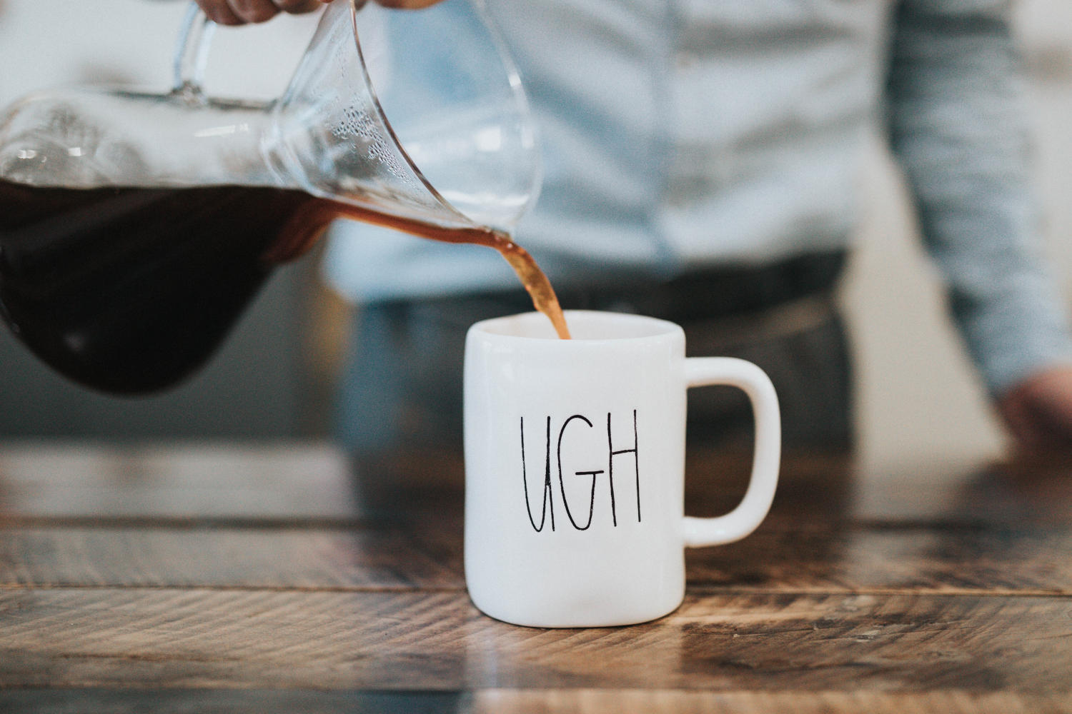 """Man pouring coffee into a mug with """"UGH"""" writting on it"""